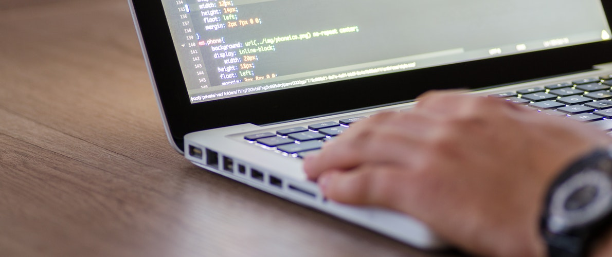 Man using a laptop with html coding